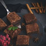 Pieces of chocolate brownie on a black round graphite plate. Top view Stock Image