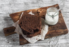 Pieces of chocolate cake and yogurt on a wooden  board Stock Images
