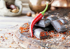 Pieces of chocolate with chili peppers on a wooden table Stock Photos