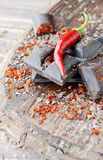 Pieces of chocolate with chili peppers on a wooden table Royalty Free Stock Photos