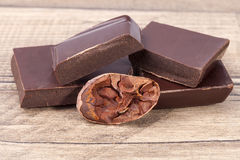 Pieces of chocolate and cocoa bean on wooden plank Royalty Free Stock Images