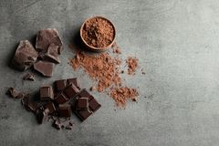 Pieces of chocolate and cocoa powder on grey background. Flat lay. Space for text royalty free stock photos