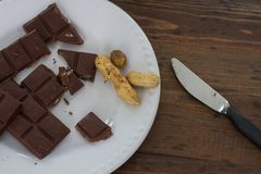 Pieces of chocolate and peanuts, a knife on a wooden brown table Royalty Free Stock Photos