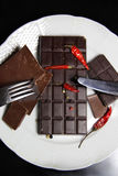 Pieces of chocolate on the plate. Pieces of chocolate with hot chili pepper Royalty Free Stock Image