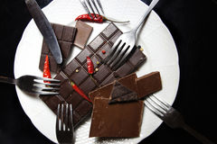 Pieces of chocolate on the plate. Pieces of chocolate with hot chili pepper Stock Photos