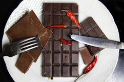 Pieces of chocolate on the plate. Pieces of chocolate with hot chili pepper Stock Images