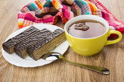Pieces of chocolate waffle cake in plate, cup of tea Stock Image