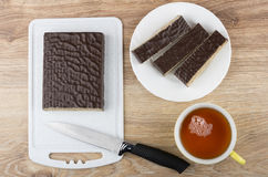 Pieces of chocolate waffle cake in white plate, cutting board Royalty Free Stock Photo