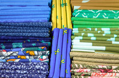 Pieces of cloth on the market. Fabric pieces of tailoring cloth on the market with different colors. Blue, black, yellow, green and brown cloth Royalty Free Stock Images