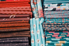 Pieces of cloth on the market. Fabric pieces of tailoring cloth on the market with different colors. Red,b rown, blue colors Stock Photo
