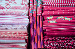 Pieces of cloth on the market. Fabric pieces of tailoring cloth on the market with different shades of pink and colorful patterns Royalty Free Stock Image