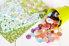 Pieces of cloth with a pattern, different buttons, green bucket Stock Photos