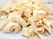 Pieces of cocoa butter. White chocolate on white paper Stock Images