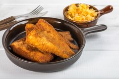 Pieces of cod in breadcrumbs. Pieces of cod in breadcrumbs on a ceramic pan Stock Images