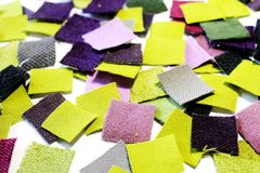 Pieces of colored cloth scattered in a chaotic manner. A variety of fabrics cut into squares, arranged in a chaotic order, the predominance of green and feulette Royalty Free Stock Photos