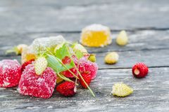 Pieces of colored marmalade in sugar and red and white strawberries on an old gray wooden table stock image