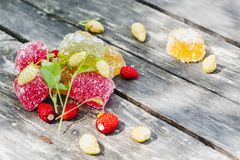 Pieces of colored marmalade in sugar and red and white strawberries on an old wooden table royalty free stock image
