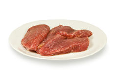 Pieces of crude meat. Lay on a white plate. On a white background Royalty Free Stock Images