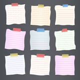 Pieces of crumpled cut colorful lined note paper are stuck on dark gray background Royalty Free Stock Images