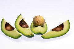 Pieces of cut fresh avocado with stone isolated on white background Stock Photos