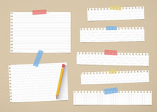 Pieces of cut out white ruled and grid notebook paper are stuck on brown background with yellow pencil Royalty Free Stock Photos