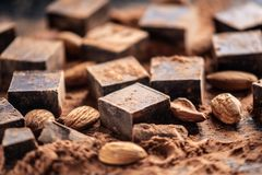 Pieces of dark bitter chocolate with cocoa and almonds nuts on wooden background. Card with space for text royalty free stock photography
