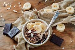 Pieces of dark chocolate and banana accompany light cereal breakfast royalty free stock photography