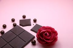 Pieces of dark chocolate bar and milk chocolate pearls and valentines rose on pink background, top view, copy space royalty free stock photography