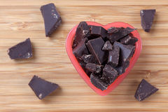 Pieces of dark chocolate in a heart bowl Stock Image