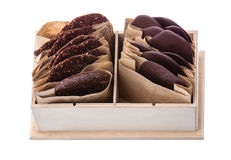 Pieces of dark chocolate in individual packaging. Pieces of dark chocolate in individual paper packaging in wooden box stock photos