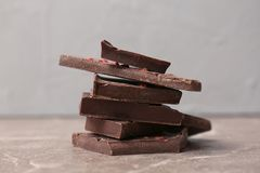 Pieces of delicious dark chocolate. On table Royalty Free Stock Images