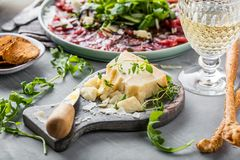 Pieces of delicious pecorino parmesan cheese with special knife. royalty free stock images