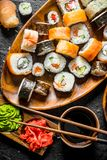 Pieces of delicious sushi, rolls and maki. On rustic background stock images