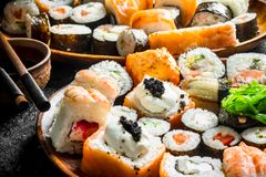 Pieces of delicious sushi, rolls and maki. On rustic background stock photography