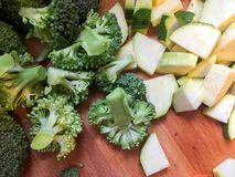 Broccoli and squash. Pieces of diced green broccoli and squash on wooden cutting board Stock Photo