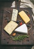 Pieces of different cheeses on a brown wooden board Royalty Free Stock Images