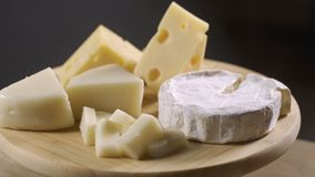 Pieces of different cheeses on plate. Rotate stock video footage