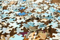Pieces of different puzzles on a glass table. Conceptual abstrac stock photos