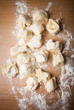 Pieces of dough on floured wooden table Royalty Free Stock Photo