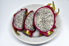 Pieces of dragon fruit on white plate stock photo