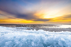 Pieces of drifting ice at sunset, IJsselmeer, Netherlands. Early morning winter landscape with sunrise and drifting ice floats near costline in the Netherlands Stock Photo