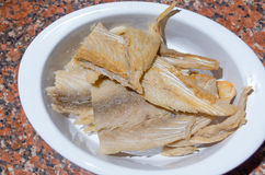 Pieces of dry fish lying on white plate drained in Stock Photography