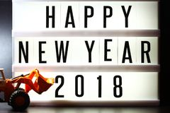 Pieces of english text spelling new year 2018 on illuminated light box. Pieces of english text spelling new year 2018 on illuminated light box in the scene Stock Photos