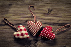 3 pieces of fabric hearts, polka dots , plaid, on wood background Stock Photography