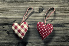2 pieces of fabric hearts, polka dots , plaid, on wood background Stock Images