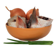 Pieces of fish and onions. The cleared, cut crude fish and onions . Everything is put in an orange, ceramic bowl Royalty Free Stock Photography