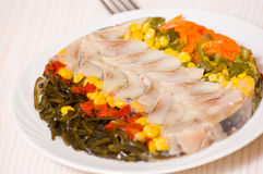 Pieces of fish with vegetables and seaweed Stock Photos
