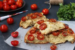 Pieces of focaccia with cherry tomatoes are located on parchment on a dark background. stock images