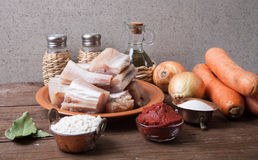 Pieces of fresh fish on a plate, vegetables, flour, tomatoe past Stock Image