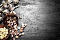 Pieces of fresh garlic in a wooden bowl. On a black chalkboard Royalty Free Stock Image